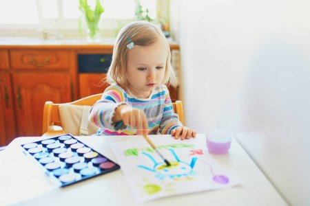 Photo for Adorable little girl painting with aquarelle at home, in kindergaten or preschool. Creative games for kids staying at home - Royalty Free Image