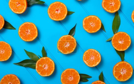 tangerines with green leaves on turquoise wooden background. Top view.