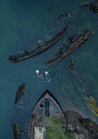 Photo pour Homme et femme sur les planches de SUP dans le cimetière du navire. Vue aérienne. Teriberka, péninsule de Kola, Russie . - image libre de droit