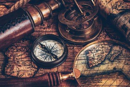 Photo pour Fond de géographie navigation concept nature morte - vieille boussole rétro vintage avec cadran solaire, spyglass et corde sur la carte du monde antique de voyage - image libre de droit