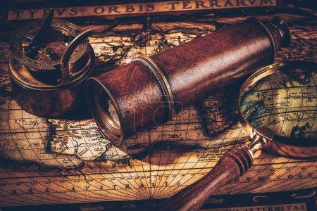 Photo pour Géographie du voyage concept de navigation nature morte arrière-plan - ancienne boussole rétro vintage avec cadran solaire, verre espion et corde sur la carte du monde antique - image libre de droit