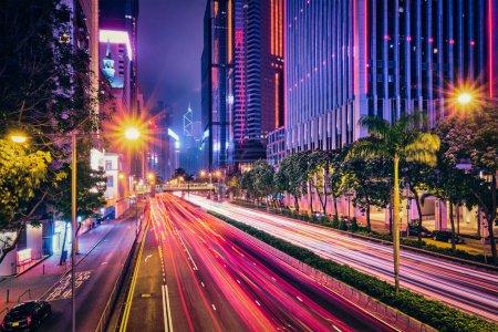 Photo pour Circulation dans la rue à Hong Kong la nuit. Bâtiments de gratte-ciel de bureau et circulation achalandée sur la route routière avec des voitures floues sentiers lumineux. Hong Kong, Chine - image libre de droit