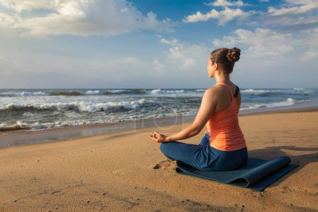 Photo for Woman doing yoga - meditating and relaxing in Padmasana Lotus Pose outdoors at tropical beach on sunset - Royalty Free Image
