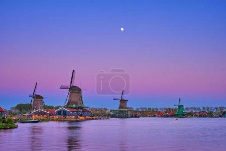 Photo pour Moulins à vent au célèbre site touristique Zaanse Schans en Hollande au crépuscule sur le coucher du soleil avec la lune. Zaandam, Pays-Bas - image libre de droit