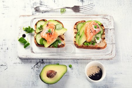 Photo for Toasts with avocado, cucumbers and salmon. Healthy eating - Royalty Free Image