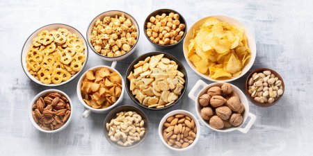 Different kinds of snacks, chips, nuts and popcorn in bowls over table background
