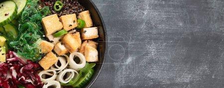 Photo pour Vue de dessus du bol végétarien au quinoa, légumes et tofu sur table sombre - image libre de droit