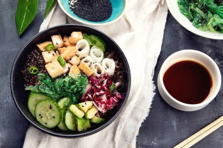 Photo pour Vue de dessus du savoureux bol végétalien avec quinoa, légumes et tofu sur table sombre - image libre de droit