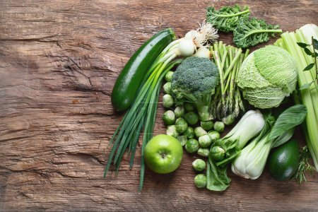 Photo for Elevated view of raw Fresh green vegetables on wooden table in kitchen - Royalty Free Image