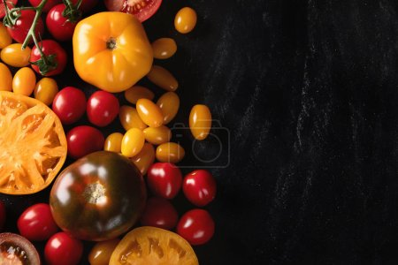 Photo for Fresh colorful tomatoes of various sizes and colors with copy space on black background. - Royalty Free Image