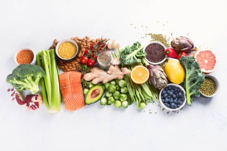 Photo for Selection of healthy food. Clean eating concept. Cooking ingredients with fish, superfood, vegetables,  artichokes, brussel sprouts, fruits, legumes  and blueberries. Top view with copy space - Royalty Free Image