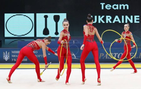 """Photo for KYIV, UKRAINE - MARCH 16, 2019: Team of UKRAINE performs with 3 Hoops and 2 Clubs during Group Competition of Rhythmic Gymnastics Grand Prix """"Deriugina Cup"""" in Palace of Sports in Kyiv, Ukraine - Royalty Free Image"""