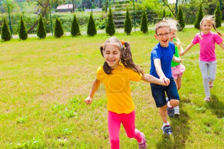 Photo for Preschoolers having fun playing together outdoors on the green grass - Royalty Free Image