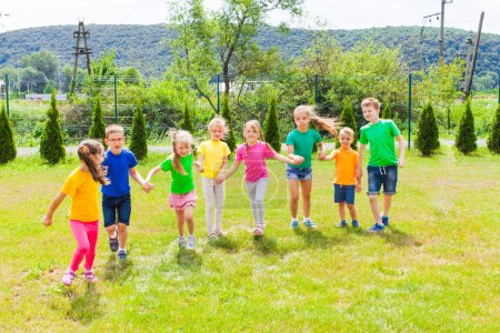 Photo for Group of kids hold their hands togeteher in colorful t-shirts having fun outdoor - Royalty Free Image