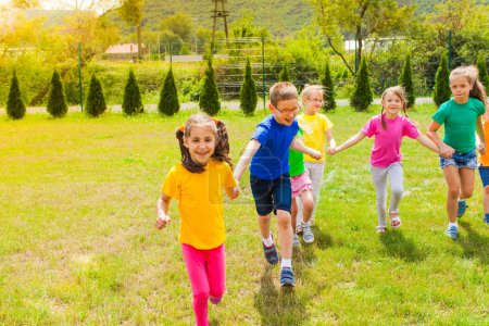 Photo for Laughing children playing outdoors in the green summer field - Royalty Free Image