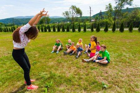 Photo pour Enfants heureux assis sur une pelouse quessing différents animaux montrés par la fille leader, lors d'un match de charades au camp d'été. Concept d'heure d'été active - image libre de droit