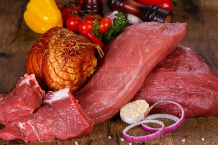 Raw beef meat over the wooden background