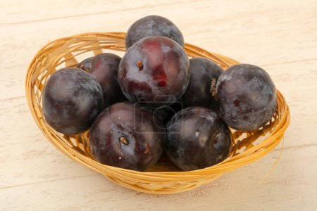 Ripe fresh plums over the wooden background