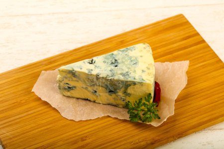 Blue cheese with parsley over wooden background