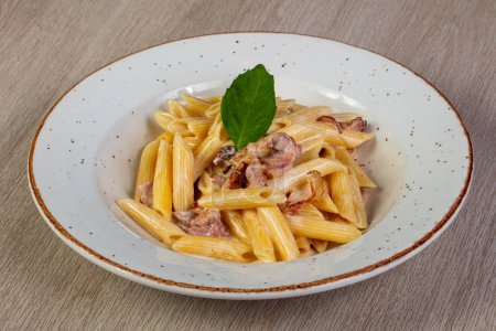 Penne with bacon and basil leaves