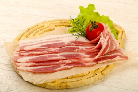 Photo for Raw bacon served dill over the wooden background - Royalty Free Image