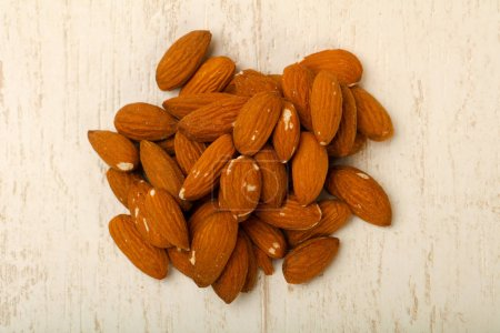 Photo for Almond nuts heap on wooden table - Royalty Free Image