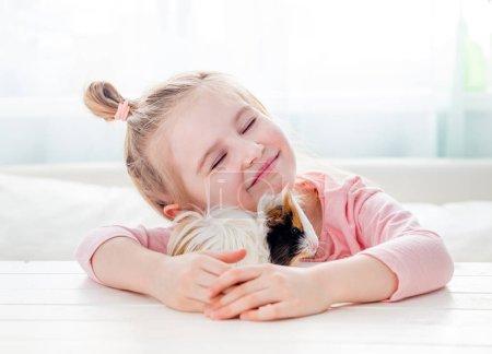 Photo pour Portrait de heureux souriant petite fille étreignant moelleux tricolore cobaye. Adorable petit enfant avec animal - image libre de droit