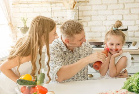 Photo for Dad with two little daughters have a fun in the kitchen - Royalty Free Image
