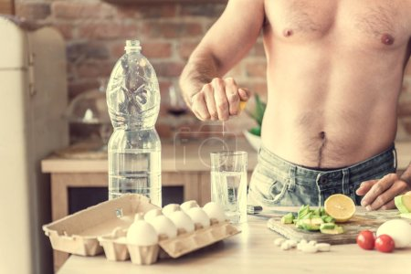 athletic man makes water with lemon in the kitchen