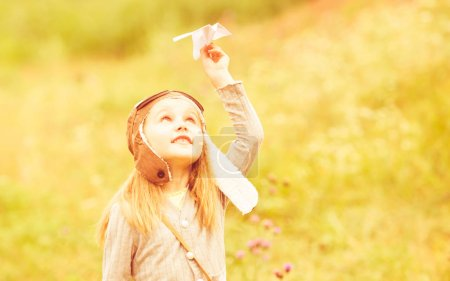 Photo for Cute little girl in helmet pilot with paper airplane outdoors - Royalty Free Image