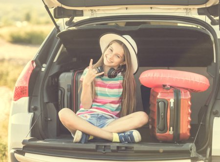 Little cute girl in the trunk of a car with suitcases