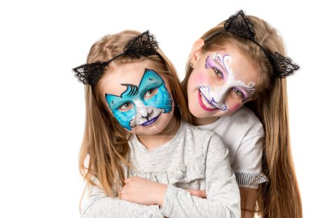 Little girls with colourful face arts hugging isolated