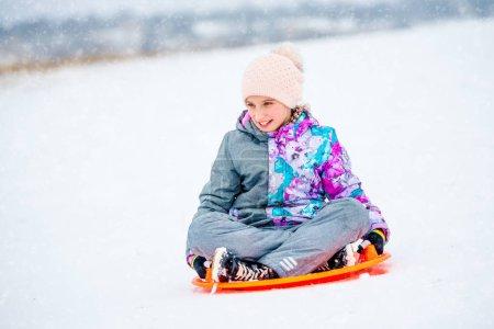 Photo pour Bonne petite fille glissant sur la colline en traîneau à soucoupe. Fille enyoing glissière tour sur la neige - image libre de droit
