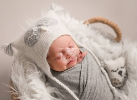 Photo for Little cute baby in white knitted beanie covered with gray coverlet sweetly sleeping on white soft blanket with toy owl in the basket - Royalty Free Image