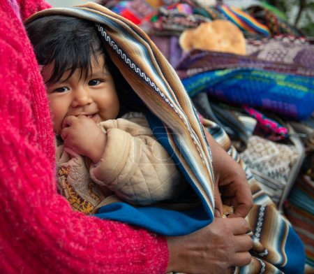 Photo pour Village du Pérou - 12 octobre 2018 : Femme tenant un petit enfant couvert d'une couverture - image libre de droit