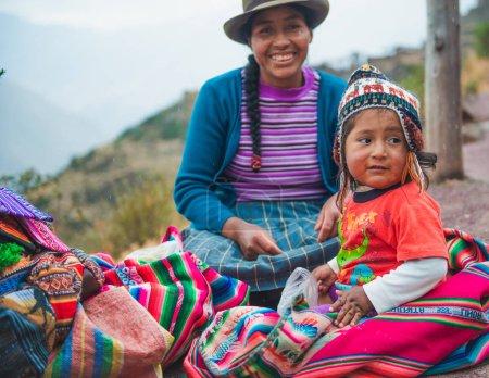 Photo pour Pérou village - 12 octobre 2018 : Femme souriante avec une petite fille assise avec un tissu coloré - image libre de droit