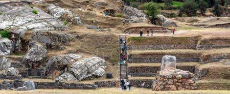 Foto de En el pueblo Saksaywaman grupos de turistas están visitando las ruinas de ruinas envejecidas de la ciudadela de piedra - Imagen libre de derechos