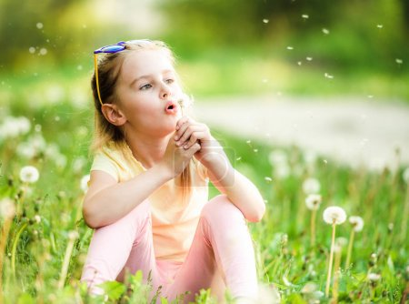 Photo for Pretty small girl likes to play with fluffy dandelions on summer meadow - Royalty Free Image