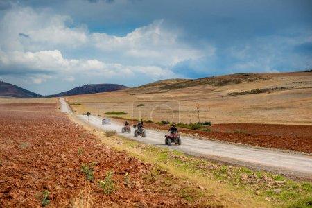 Photo pour Une escouade de cyclistes courageux traverse une vallée sablonneuse au Pérou - image libre de droit
