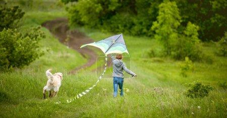 Photo pour Vue arrière de la petite fille avec chien mignon volant cerf-volant coloré sur la nature printanière - image libre de droit