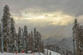 Cloudy and misty weather on ski resort. Mountain winter landscape