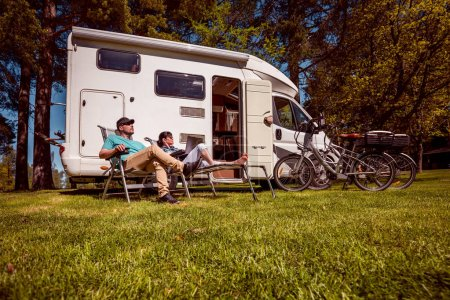 Woman with a man resting near motorhomes in nature. Family vacation travel, holiday trip in motorhome RV, Caravan car Vacation.