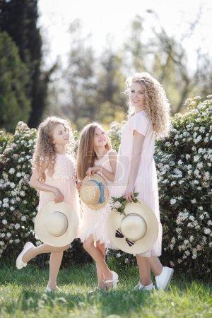 Photo pour La sœur aînée et ses deux sœurs cadettes passent le temps à l'extérieur dans un magnifique parc avec des arbustes à fleurs pour un jour de printemps ensoleillé. Trois sœurs en robes roses pâles avec des chapeaux de paille à la main sur un fond de fleurs - image libre de droit
