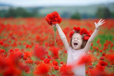 Photo pour Une petite fille dans une couronne rouge de fleurs fraîches marchant sur le champ de pavot par une journée d'été ensoleillée. Jolie fille gaie 5-6 ans dans une robe blanche sur une immense prairie de coquelicots rouges en fleurs, posant seul un jour d'été au coucher du soleil - image libre de droit