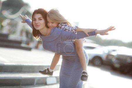 Photo pour Mère et fille dehors en ville. jouer et s'amuser. Mode mère heureuse et fille enfant s'amusent ensemble dans la ville.Mère avec petite fille charmante sont assis dans la ville en plein soleil. Des émotions réelles . - image libre de droit
