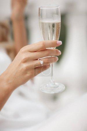 Photo pour Bague de mariage et de fiançailles à portée de main avec champagne. main de femme avec un verre de vin mousseux. Photo de haute qualité - image libre de droit