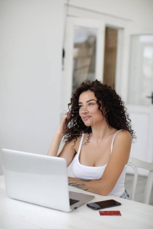 Photo for Young woman working at home with laptop shopping and surfing internet. High quality photo - Royalty Free Image