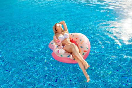 Photo for Summer Vacation. Enjoying suntan Woman in bikini on the inflatable mattress in the swimming pool with coctail. - Royalty Free Image