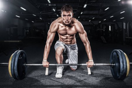 Photo for Athletic shirtless young sports man - fitness model holds the barbell in gym. - Royalty Free Image