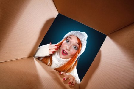Photo for Smiling young girl opening a carton box and looking inside, relocation and unpacking concept - Royalty Free Image